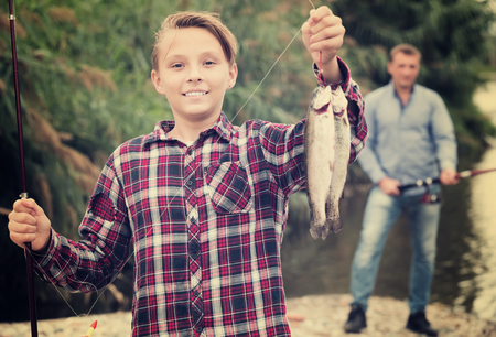 Smiling teenage boy releasing catch on hook fish on forest Stock Photo