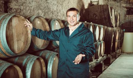 laboratorian: Man wine house technician working in storage with wooden barrels