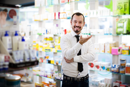 Positive male customer searching for reliable drug in pharmacy