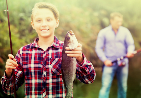 Glad teenager boy showing catch fish he holding in hands Stock Photo
