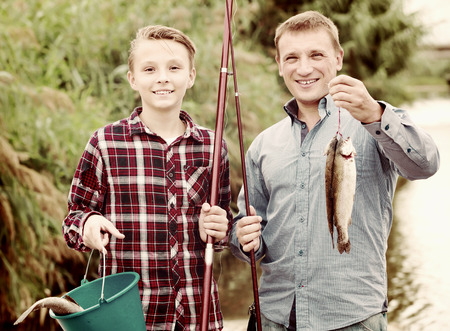 gudgeon: Portrait of friendly father with teenager son looking at fish on hook in hands outdoors
