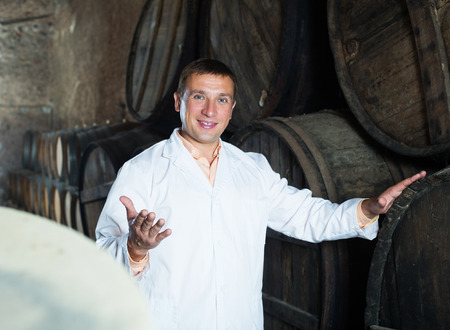 ageing process: Glad man in robe checking ageing barrel process of wine Stock Photo