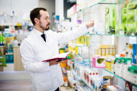 Glad adult man pharmacist writing down assortment of drugs in pharmacy