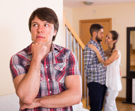 Jealous husband watching spouse flirting with friend at home