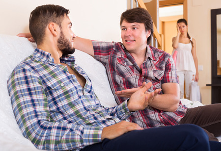 unfaithfulness: Wife watching partner having double talk with male friend Stock Photo