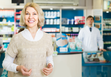 Portrait of positive mature woman chooses drugs at the pharmacy Stock Photo