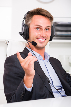 Cheerful adult man talking on headset at company office