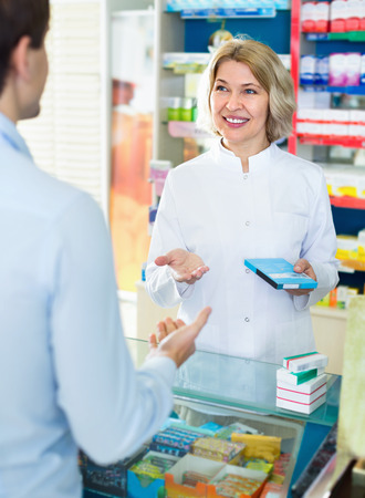 Friendly smiling female pharmacist counseling customer about drugs usage in modern farmacy Stock Photo
