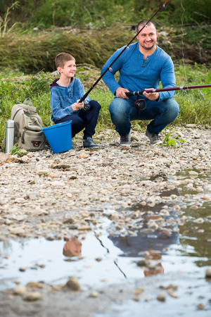 manhood: happy smiling father and teenager son fishing together in wild river Stock Photo