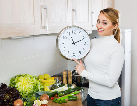domestic kitchen: Portrait of smiling woman holding clocks in domestic kitchen