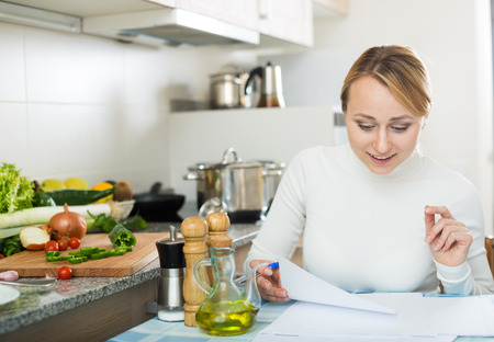 domestic kitchen: Happy female signing agreement in domestic kitchen and smiling