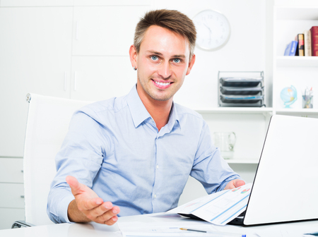Portrait of cheerful man employee holding blank document in hands in office Standard-Bild