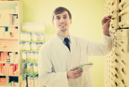 depot: Positive adult male pharmacist posing in pharmacy depot