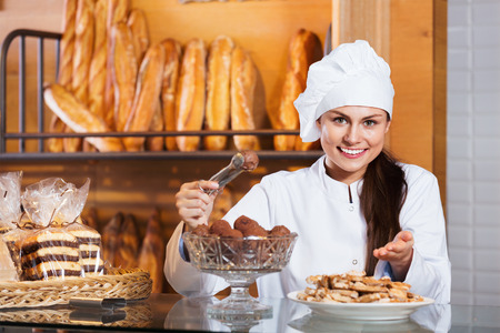 Portrait of friendly charming young woman at bakery display with pastry