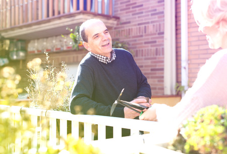 Portrait of retired couple on a terrace: old husband is holding a cup of hot beverage and talking to his wife who is holding gardening tools Stock Photo