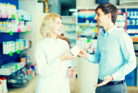 Helpful pharmacist serving and consulting man in pharmacy