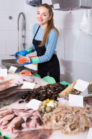 happines: portrait of girl posing near display with cooled fish and seafood