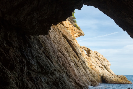 View from grotto at Mediterranean coast at sunny day in summer