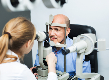 Smiling friendly positive female optician doing eye examination with aid of slit lamp Stock Photo