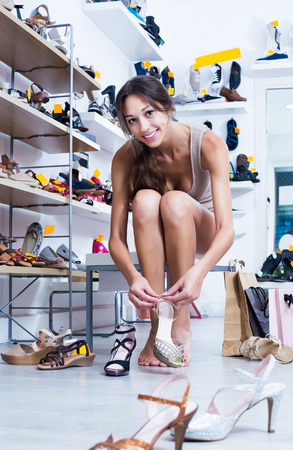 Positive young brunette girl customer trying on chosen shoes in footwear department Stock Photo