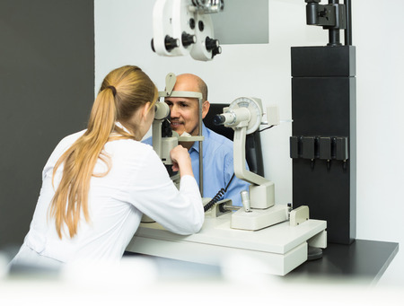 Friendly female ophthalmologist and happy european mature patient checking eyesight in clinic Stock Photo