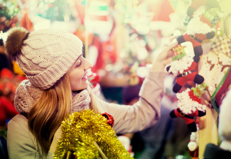 overspending: Happy girl in winter outwear near counter choosing gifts at Christmas market in evening time