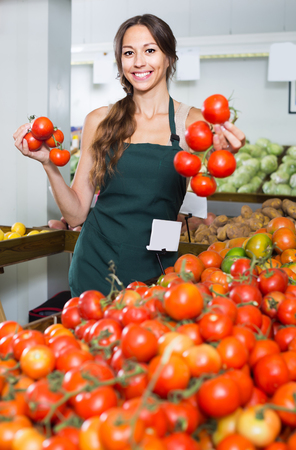 Young female seller wearing apron holding fresh ripe tomatoes on market Stock Photo