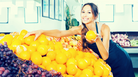 Adult woman seller wearing apron holding orange in hand in fruit store Stock Photo