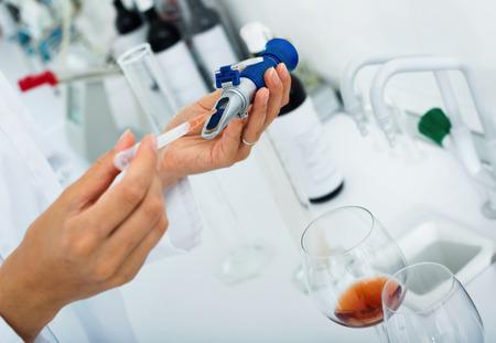 diligente: Ver en las manos hábiles de trabajo en el laboratorio de química comprobar las cualidades del vino