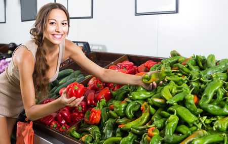 smiling young woman taking fresh red and green paprika on fruit market