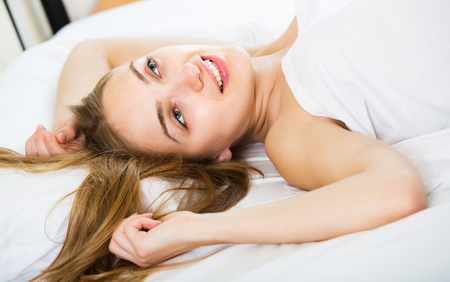 Happy young girl lying in bed with opened eyes and smiling