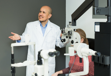 advise: Ophthalmologist and patient checking eyesight in clinic Stock Photo