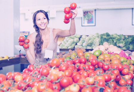 cheerful young woman customer holding fresh ripe tomatoes on supermarket