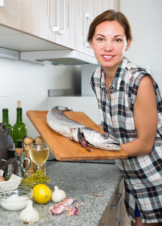 Portrait of woman having cutting board with fresh hake fish in hands on kitchen