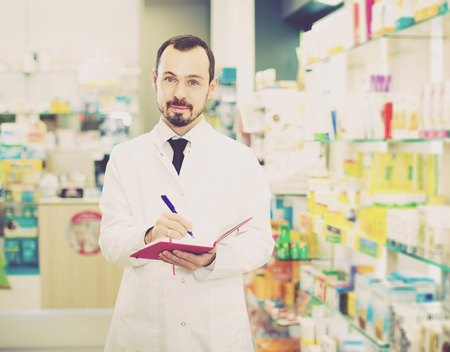 prescribed: Glad adult pharmacist writing down assortment of drugs in pharmacy