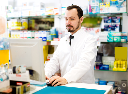 prescribed: Smiling male pharmacist checking assortment of drugs in pharmacy