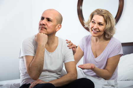 remit: Mature  american wife warmly comforting upset husband in bedroom