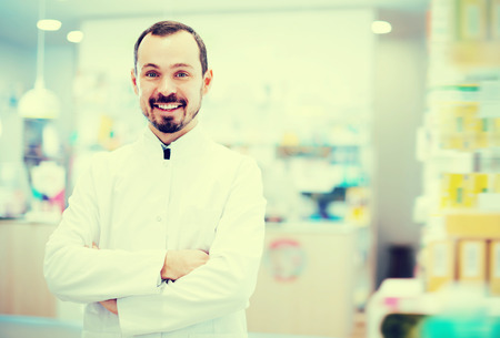 prescribed: Handsome pharmacist showing assortment of drugs in pharmacy Stock Photo