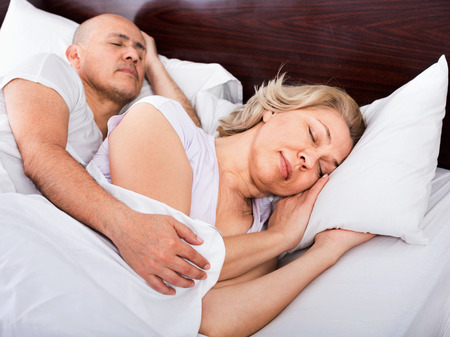 spanish home: Portrait of pleasant mature couple napping in bed with closed eyes