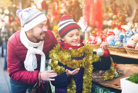 overspending: little girl with dad buying decorations for Xmas Stock Photo