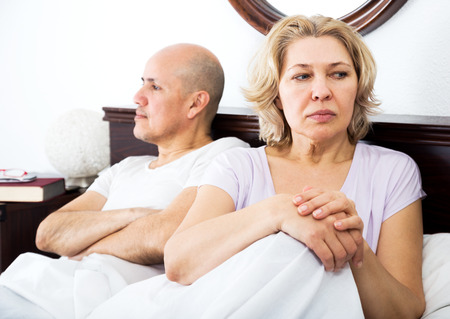 scandals: Elderly man and sadness woman getting through scandals and blamings in bedroom