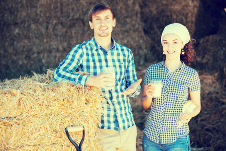 portrait of two young happy farmers taking a pause in the hay and having a glass of milk in hands Stock Photo