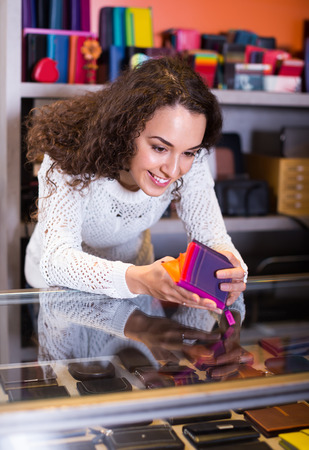 Portrait of cheerful young brunette selling wallets and purses in store Stock Photo