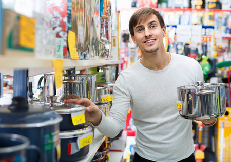 Happy smiling young man buying new metallic pan in household store