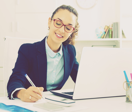 Positive business lady sitting at office desk with laptop Stock Photo