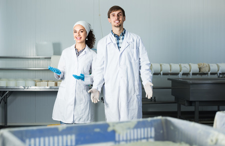 technologists: Two friendly smiling technologists in lab coats showing their production process at dairy farm lab