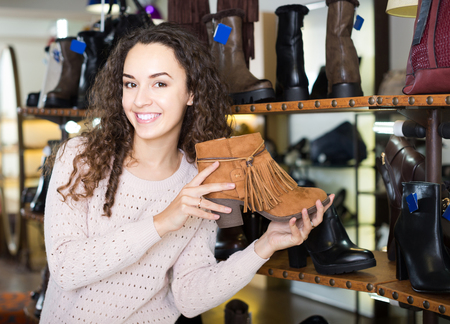 comprando zapatos: young female buying winter female shoes in  shoe store