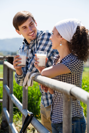 Positive man and woman standing with the fence and drinking milk
