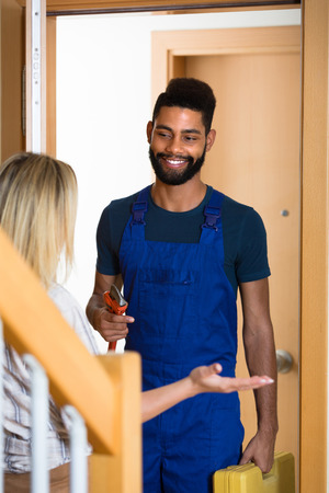 blue overall: Blonde girl meeting smiling African handyman in blue overall at the doorway