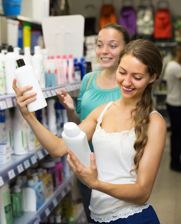 Two smiling young women choosing shampoo at supermarket. Selective focus